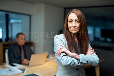 Buy stock photo Portrait of a mature businesswoman standing in an office at night with her colleague in the background