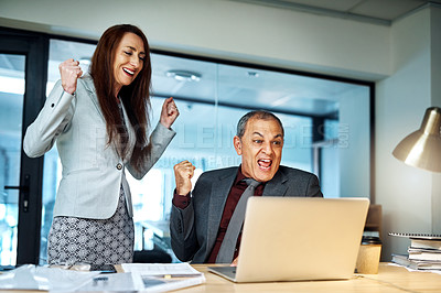 Buy stock photo Shot of two businesspeople cheering while working together on a laptop in an office at night