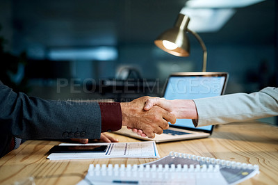 Buy stock photo Closeup shot of two businesspeople shaking hands in an office at night