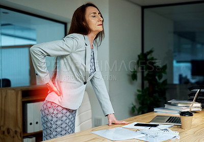 Buy stock photo Shot of a mature businesswoman suffering with back pain while working in an office at night