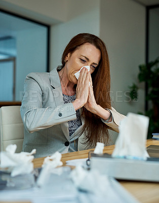 Buy stock photo Shot of a mature businesswoman blowing her nose while working in an office at night
