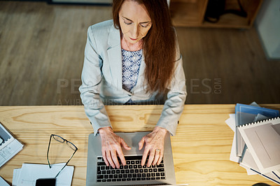 Buy stock photo High angle shot of a mature businesswoman using a laptop in an office at night