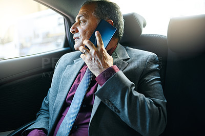 Buy stock photo Shot of a mature businessman talking on a cellphone while traveling in the backseat of a car