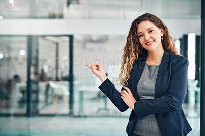 Buy stock photo Portrait of a young businesswoman pointing in an office