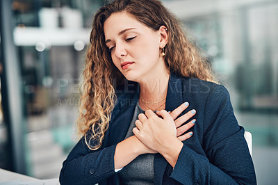 Buy stock photo Shot of a young businesswoman holding her chest in pain while working in an office
