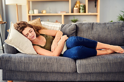 Buy stock photo Shot of a young woman suffering from stomach cramps on the sofa at home