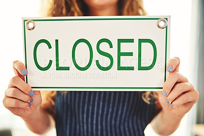 Buy stock photo Cropped shot of a woman hanging up a closed sign in her store