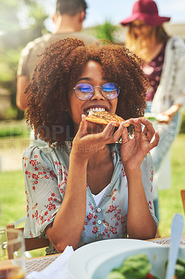 Buy stock photo Portrait of a carefree young woman having a slice of pizza outside with friends during lunch