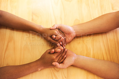 Buy stock photo Cropped shot of two unrecognizable people holding hands in support inside at home during the day