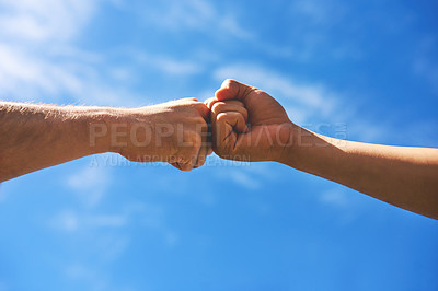 Buy stock photo Low angle shot of two unrecognizable people pounding fists together in agreement outside during the day