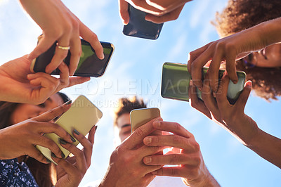 Buy stock photo Low angle shot of a group of cheerful friends texting on their cellphones outside during the day