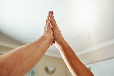 Buy stock photo Cropped shot of two unrecognizable people giving each other a high five inside during the day