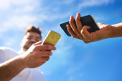 Buy stock photo Low angle shot of two unrecognizable young people standing together while texting on their cellphones outside during the day
