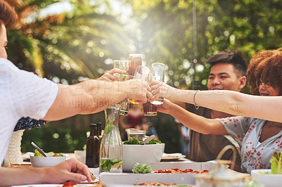Buy stock photo Cropped shot of a cheerful group of young friends engaging in a celebratory toast with drinks outside at a lunch table
