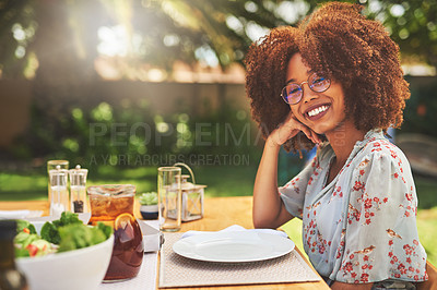 Buy stock photo Portrait of a cheerful young woman seated at a lunch table patiently waiting for food outside during the day