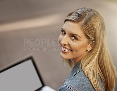 Buy stock photo Cropped portrait of an attractive young female student using her laptop while sitting alone on campus