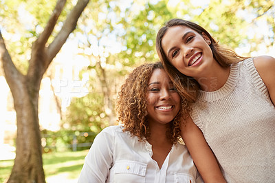 Buy stock photo Cropped portrait of two attractive young female students enjoying their free time together on campus