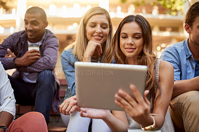 Buy stock photo Cropped shot of a group of two young female students using a digital tablet while enjoying their free time on campus