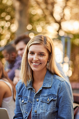 Buy stock photo Cropped portrait of an attractive young female student siting outdoors on campus with her classmates in the background