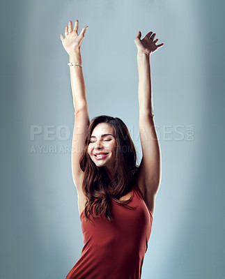 Buy stock photo Studio shot of a cheerful young woman posing with her arms outstretched against a blue background