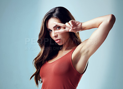 Buy stock photo Studio portrait of an attractive young woman doing the peace sign pose against a blue background