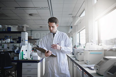 Buy stock photo Shot of a young scientist recording the findings of an experiment in a modern laboratory