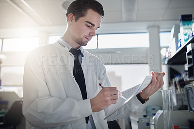 Buy stock photo Shot of a young scientist completing paperwork while working in a laboratory