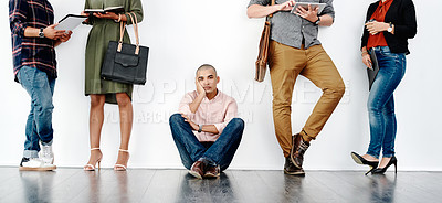 Buy stock photo Full length shot of a young businessman sitting down on the floor while waiting in line for an interview