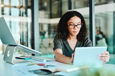 Buy stock photo Cropped shot of a young woman using a digital tablet while sitting at her desk