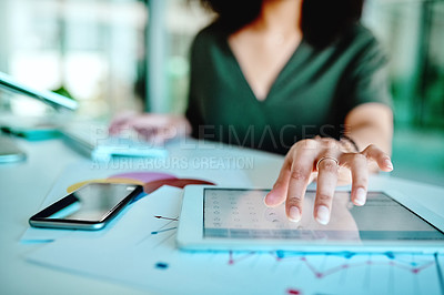Buy stock photo Cropped shot of an unrecognizable businesswoman using a digital tablet at her desk