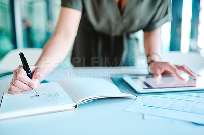 Buy stock photo Cropped shot of an unrecognizable businesswoman writing while looking at something on a digital tablet