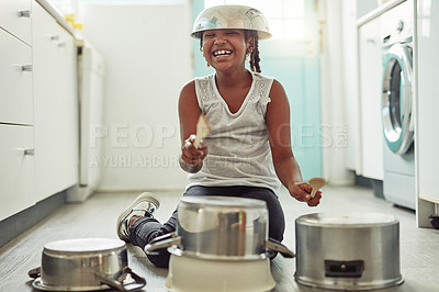 Buy stock photo Shot of a little girl playing drums on a set of pots in the kitchen