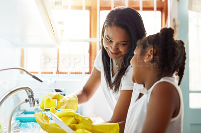 Buy stock photo Cropped shot of a young girl helping her mother with the dishes