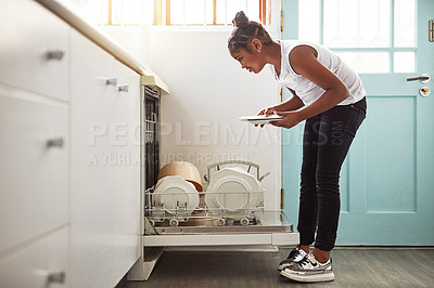 Buy stock photo Shot of a young girl packing dishes in the dishwasher