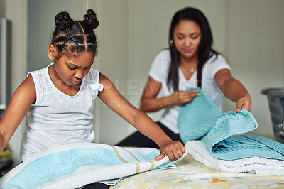Buy stock photo Shot of a young girl helping her mother to fold clean washing