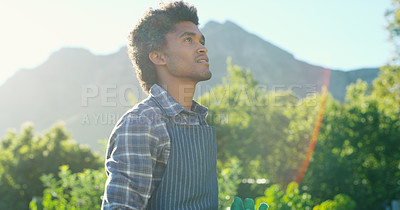Buy stock photo Cropped shot of a handsome young male farmer working out in the fields on his farm