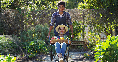 Buy stock photo Cropped portrait of a handsome young male farmer pushing his wife around in a wheelbarrow while working on their farm