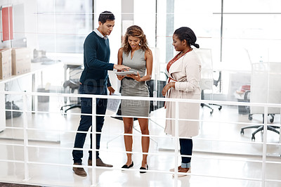 Buy stock photo Full length shot of a young diverse group of colleagues at work discussing ideas on a tablet in the office