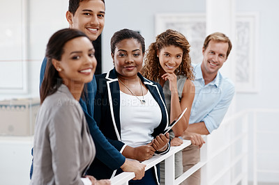 Buy stock photo Cropped shot of a diverse group of colleagues standing together in the office and smiling at the camera