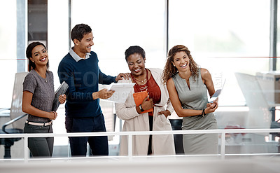 Buy stock photo Shot of a happy young group of colleagues sharing a laugh together in the office