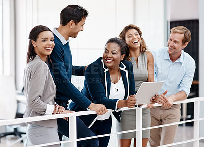 Buy stock photo Cropped shot of a happy diverse group of colleagues sharing a laugh together in the office