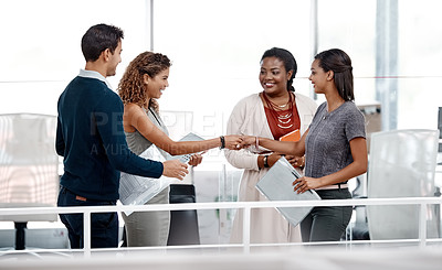 Buy stock photo Shot of a diverse young group of colleagues shaking hands in agreement at the office