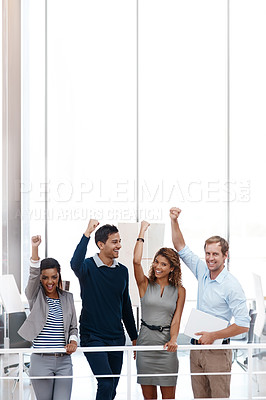 Buy stock photo Shot of a diverse group of colleagues celebrating success with their arm raised at the office
