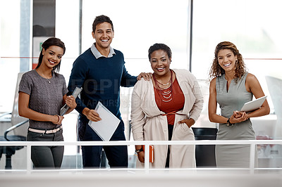 Buy stock photo Shot of a young diverse group of colleagues standing together in the office and smiling at the camera