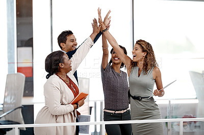 Buy stock photo Cropped shot of a young diverse group of colleagues raising an arm for a high five in the office