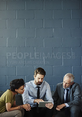Buy stock photo Cropped shot of three businesspeople working together on a digital tablet in their office
