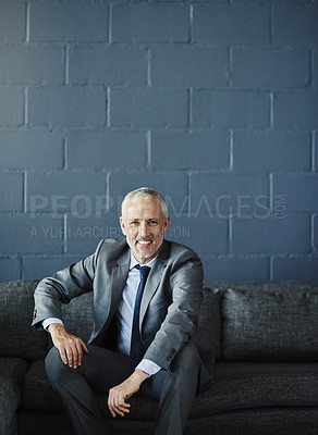 Buy stock photo Cropped portrait of a handsome and successful mature businessman sitting on a sofa in his office