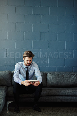Buy stock photo Full length shot of a handsome young businessman using his tablet while sitting on a sofa in the office
