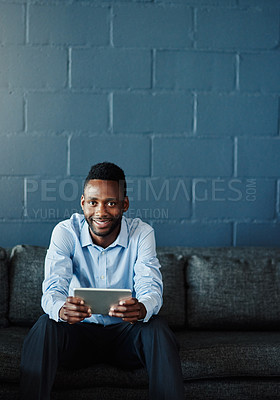 Buy stock photo Cropped portrait of a handsome young businessman using his tablet while sitting on a sofa in the office
