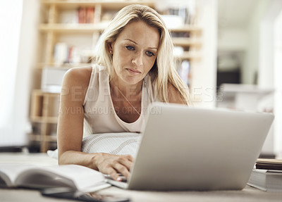 Buy stock photo Cropped shot of a beautiful mature woman lying on her living room floor using a laptop